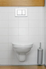 toilet with white walls and brush