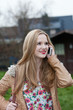 Young Blond Woman Talking on Cell Phone Outdoors