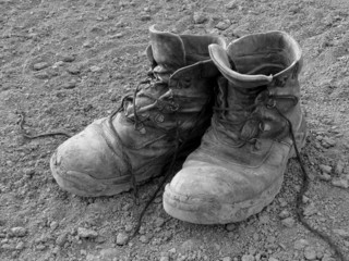 pair of well worn work boots in black and white