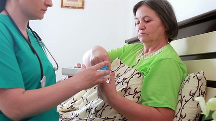 Home caregiver giving medicine to senior woman