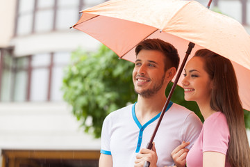 Portrait of woman and man standing under umbrella.