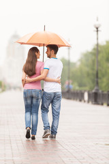View of couple back under umbrella walking.