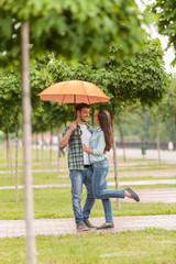 young couple standing under umbrella in park.