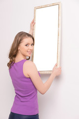 Young woman hanging mirror on wall.