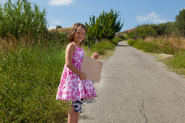 little girl hitchhlikes on the road in the nature