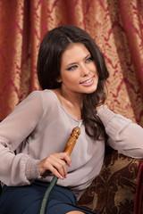 Beautiful young woman smoking hookah.