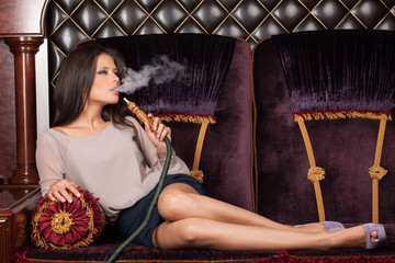 Beautiful young woman inhaling hookah.