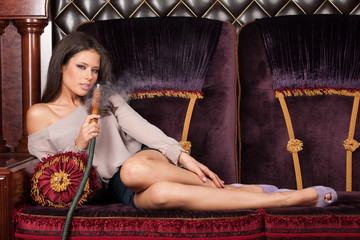 Beautiful young woman lying and smoking hookah.