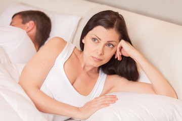 unhappy woman lying in bed stressed.