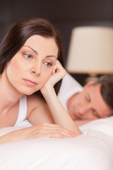 closeup of unhappy woman lying in bed stressed.