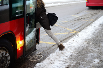 Woman entering bus in winter