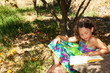 a beautiful little girl reading a yellow book in the garden with