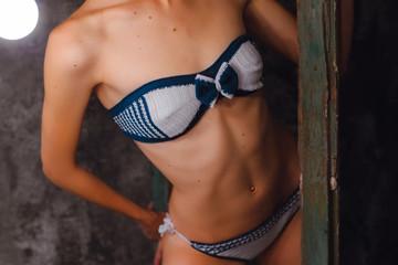Body of model in a dark  blue with white knitted bikini