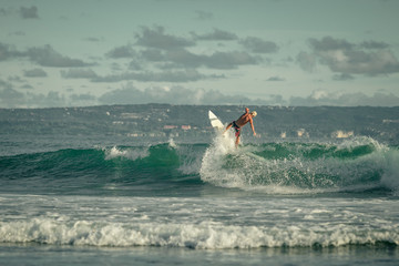 Surfer riding large  ocean wave at the day time