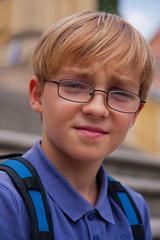 Mały chłopiec w okularach i z plecakiem na wycieczce