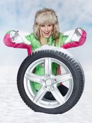 Woman with winter tyres in the snow