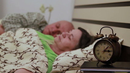 Senior couple in bed sleeping. Focus on watch.