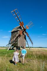 Zwei Kinder betrachten eine alte Windmühle