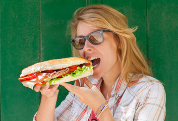 Young woman eating fast food sandwich