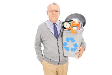 Senior man holding a recycle bin full of old stuff