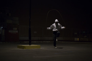 Hooded athlete skipping under a street light at night