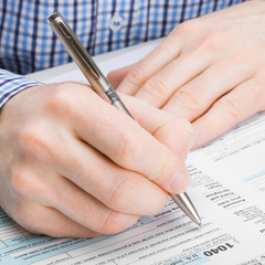Male filling out 1040 US Tax Form - 1 to 1 ratio