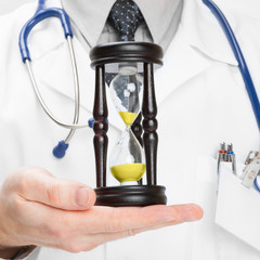 Doctor holdling in his hand a hourglass - 1 to 1 ratio
