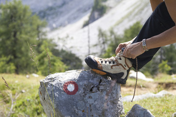 Cute female hiker tying boot laces on rock with signpost