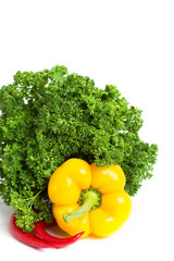 Yellow bell pepper and chili pepper in green curly parsley close