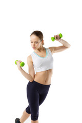 Sporting young woman is engaged with dumbbells