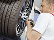 canvas print picture - Motor mechanic is changing a tyre with new alu rim