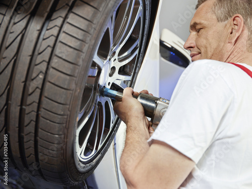 canvas print picture Motor mechanic is changing a tyre with new alu rim
