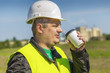 Worker with cup of coffee on a factory background