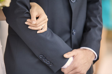 Woman's hand holding man's arm