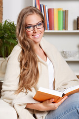 Beautiful young woman reading a book in glasses