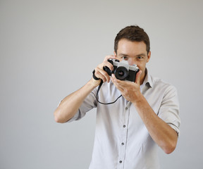 Photographer on grey background with vintage camera