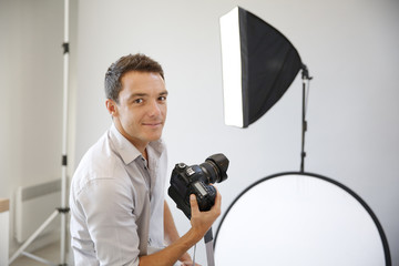 Photographer in studio with lighting equipment