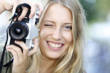 Beautiful cheerful girl using vintage photo camera