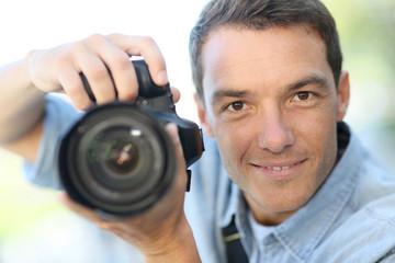 Photographer using reflex camera outside