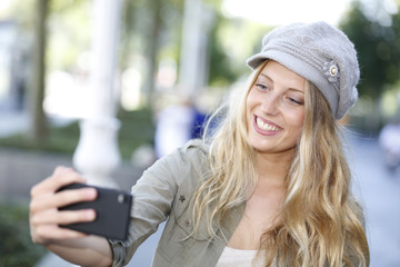 Trendy girl with hat taking picture with smartphone