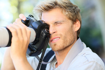 Young photographer shooting with digital camera