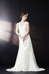 Glamorous bride in wedding dress, looking away.