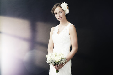 Stunning young bride holding bouquet.