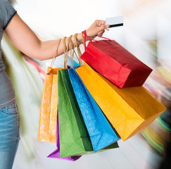 Woman holding shopping bags and credit card