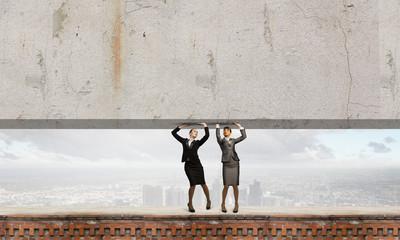 Women lifting wall