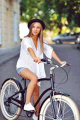 Young woman on a bicycle outdoor portrait