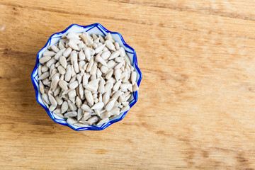 Bowl of fresh  sunflower seeds on wooden table background.