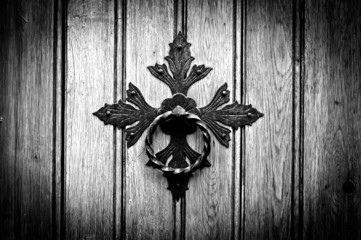 Antique door knocker on old door. Black and white photo