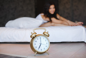 Young woman with alarm clock on the bed at the morning