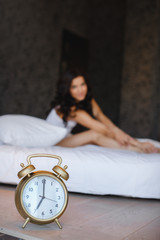 A young woman with an alarm clock on the bed in the morning